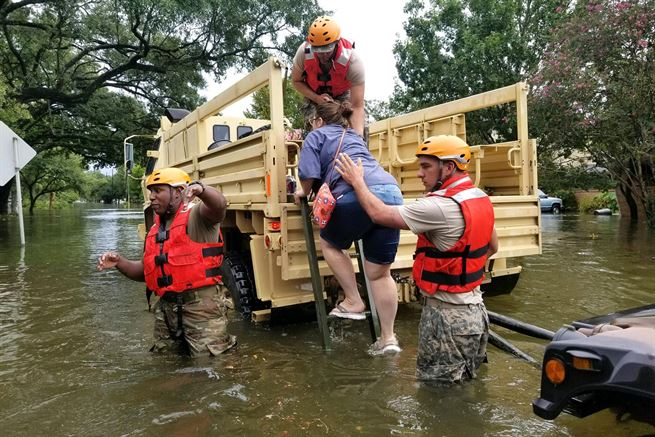 Texas National Guardsmen assist residents into a military vehicle during Hurricane Harvey flooding in Houston, Texas, Aug. 27, 2017. Army National Guard photo by Lt. Zachary West